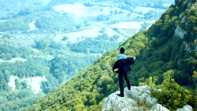 Man on top of mountain. Successful man showing satisfaction video