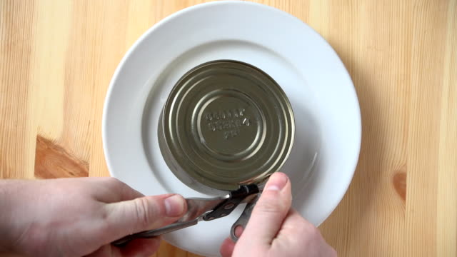 Man opening a tin of canned food using a manual can-opener. video