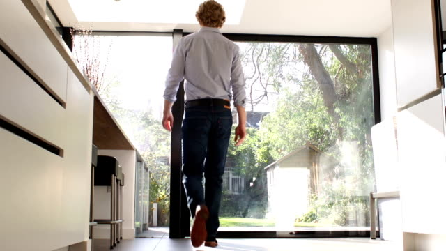 Man opening large glass door to look outside video