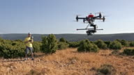 Man operating a drone on sunny mountain top video
