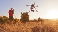 DS Man operating drone taking off the hill into sunset video