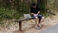Man outdoors with laptop computer working on vacation video