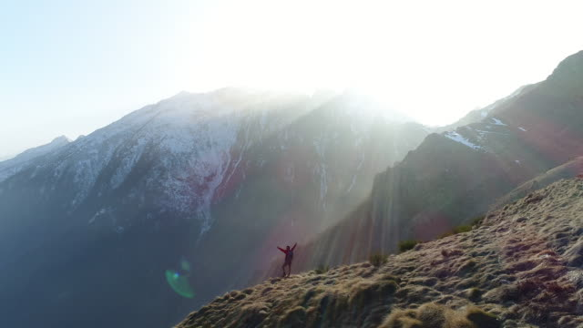 Man outstretches arms on top of mountain video