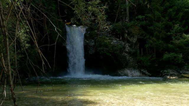 SLOW MOTION: Man paddling his kayak through raging whitewater waterfall video
