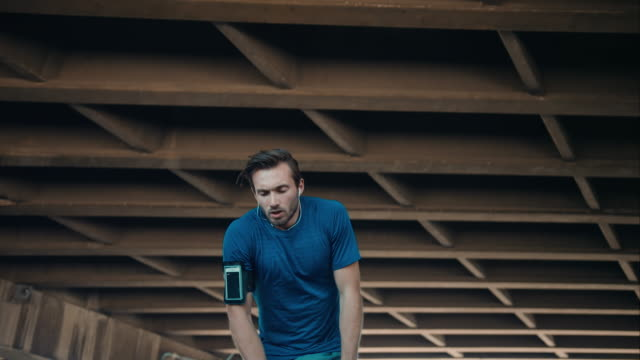 Man pauses jogging in urban setting video