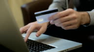 Man paying bill, shopping online, inserting credit card number. A man paying for online shopping using laptop and credit card. close up video