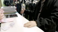 Man pays money in cash in the clothing store shop video