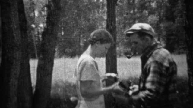 1935: Man photographs woman holding up recently caught trout fish. video