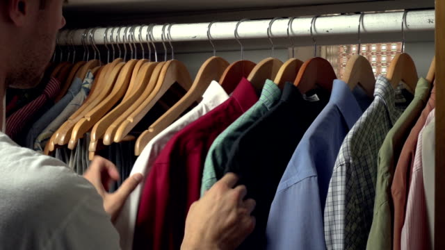 Man picking out a shirt to wear from his closet video