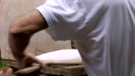 A man places home made matzah in a wood fired oven in slow motion video