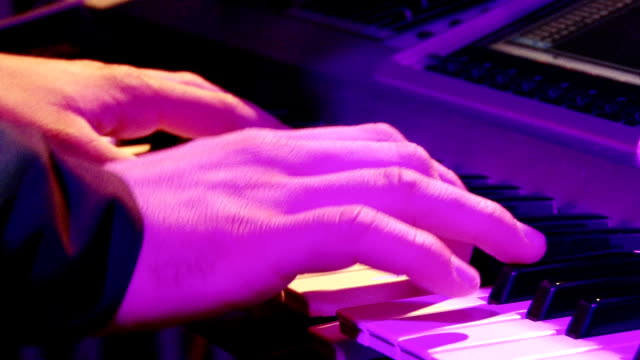 Man play music keyboard, colorful light video