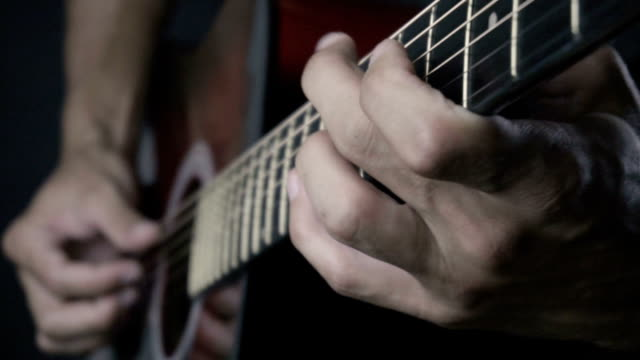 Man playing acoustic guitar on black background with fingers in slow motion video