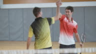 Man playing doubles indoor badminton doing a serve video
