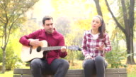 Man playing guitar and singing with women while sitting on bench in park video