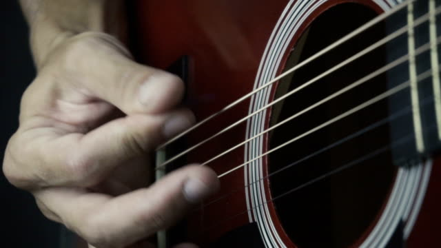 Man playing guitar on black background. Six strings. Playing with fingers video