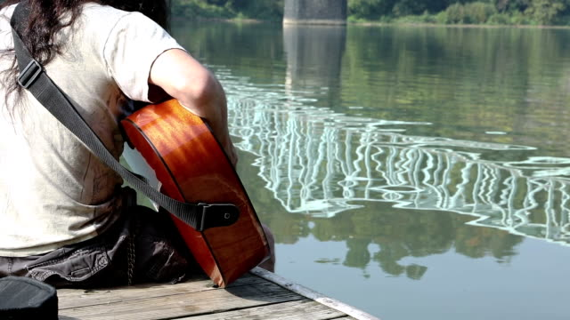 Man Playing Guitar on Boat Dock video