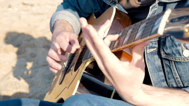 Man playing guitar on the beach, slow motion video