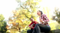 Man playing guitar while woman singing, sitting next to him on bench in park video