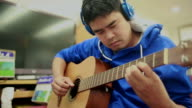 Man Playing Guitar with headphones. video