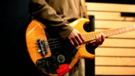 Man playing old, worn out bass guitar video