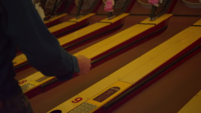 A man playing skee ball video