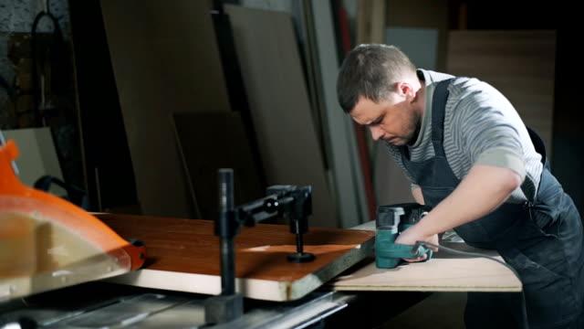 Man polishing wood with electrical sanding machine video