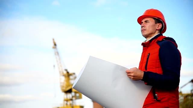man portrait builder architect in orange helmet looks instruments project against blue sky and building video