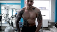 Man posing in the gym. Slow motion. video