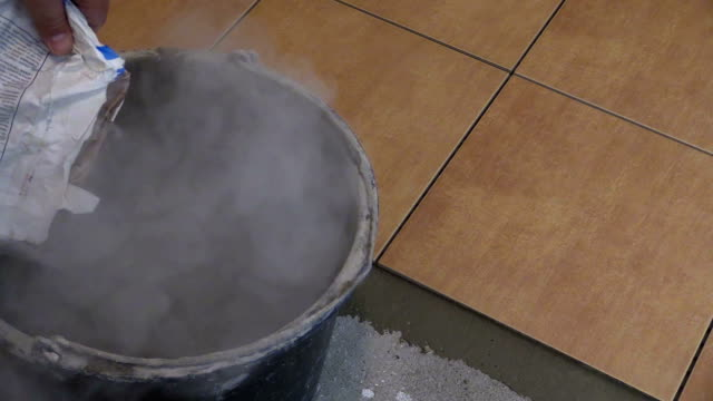 Man pour special tile glue mixture to bucket. Closeup shot video