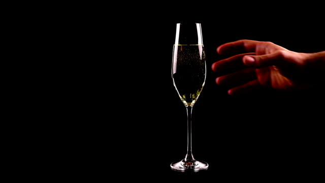 man pouring champagne on black table against black background, not drink and drive video