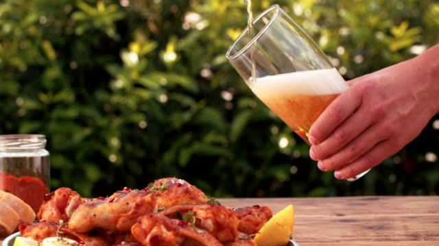 Man pouring glass of beer with chicken wings in foreground video