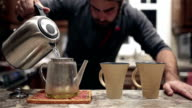 Man pouring hot water into tea jar video