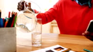 Man pouring jug of water in glass while using mobile phone video