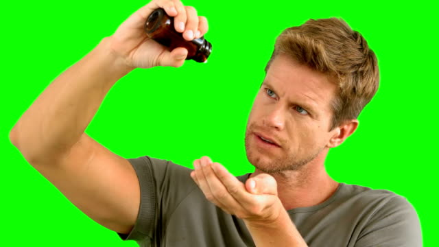 Man pouring out pills on green screen video