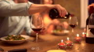 Man pouring some red wine at a dinner party video