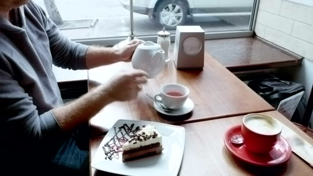 Man pours tea from teapot spills and wipes table video