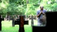 Man praying at cemetery video