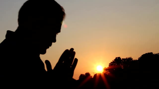 Man Praying at Sunset video