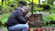 Man praying on bench with the rosary at outdoors church video