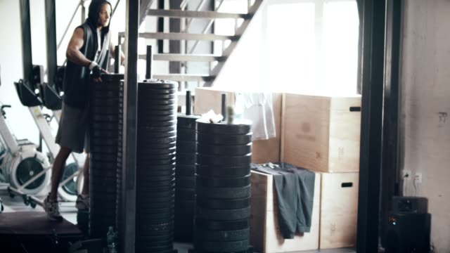 Man preparing weights for exercising video