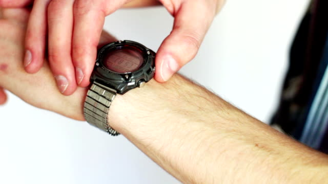Man presses a button on the electronic wristwatch his arm video
