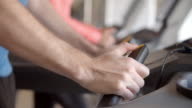 Man pressing buttons on a running machine at gym, detail video