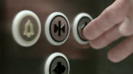 Man pushes a button opening elevator doors. Close up video