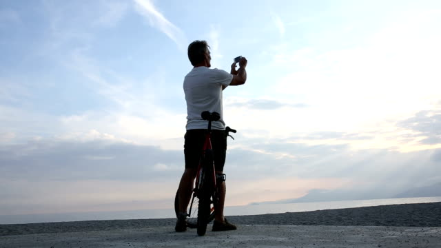 Man pushes bicycle onto beach, takes picture out to sea video