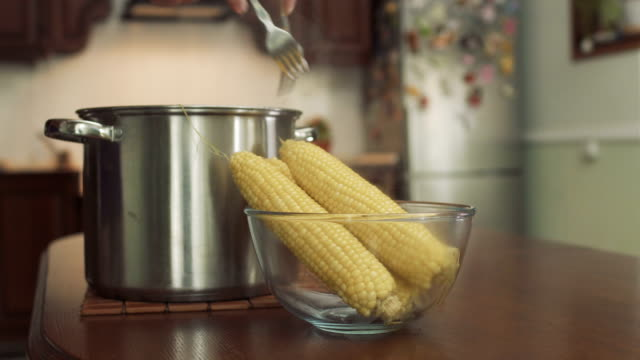 Man put the cooked hot corn into a glass bowl video