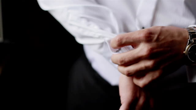 Man puts cufflinks on sleeves of white shirt. Close-up video