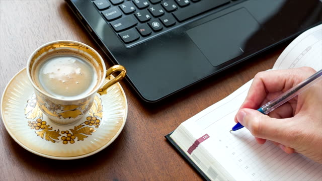 Man puts cup on table and writes in notebook. video