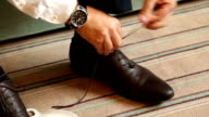 Man puts on shoes. Focus on the laces video