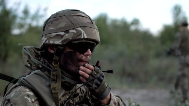 Man putting camouflage on face video