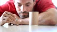 Man putting coins into a savings bin video
